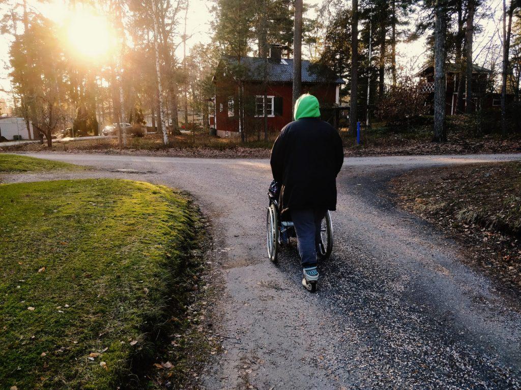 Takaapäin kuvattu henkilö työntää pyörätuolissa olevaa toista henkilöä pitkin hiekkatietä. Maisemassa näkyy risteys, havupuita ja punaisia puurakennuksia. Auringon valo siivilöityy puiden läpi.