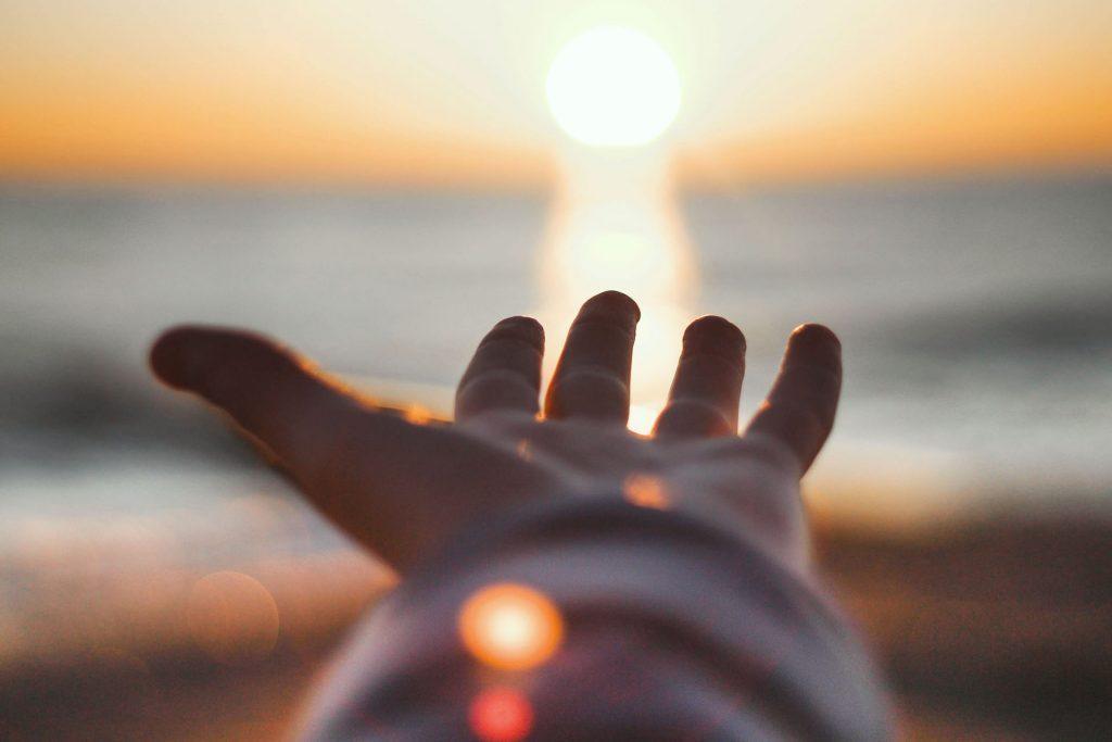Käsi ojentuu kohti auringonlaskua.