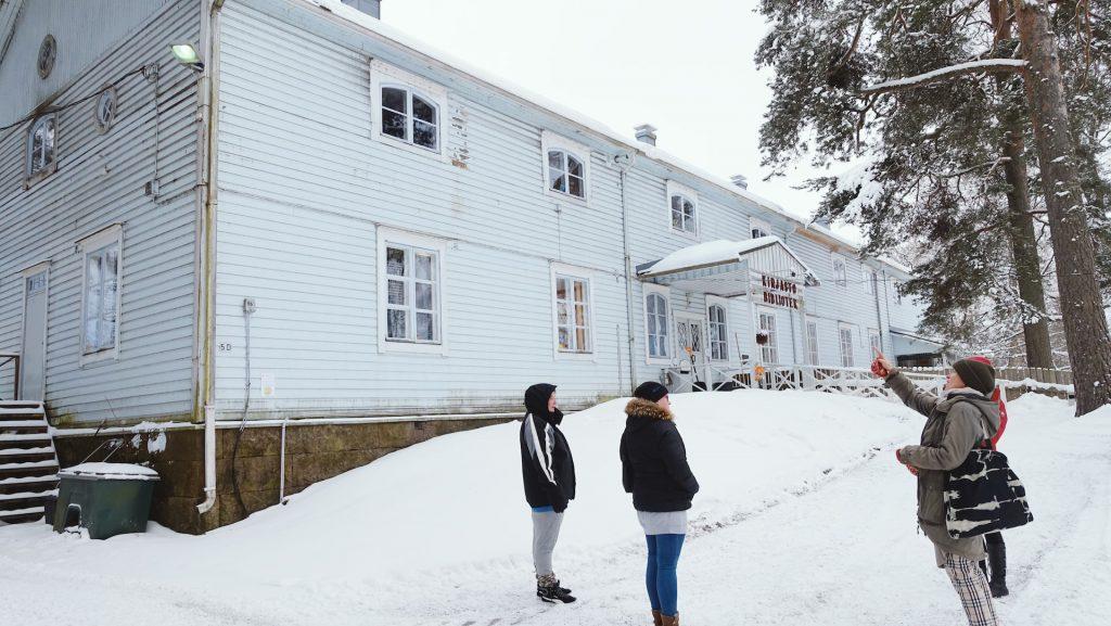 Perinnetalkoot-hankkeen työntekijöitä Lapinjärven vanhan maamieskoulun vaaleansinisen puurakennuksen edustalla lumisessa maisemassa.