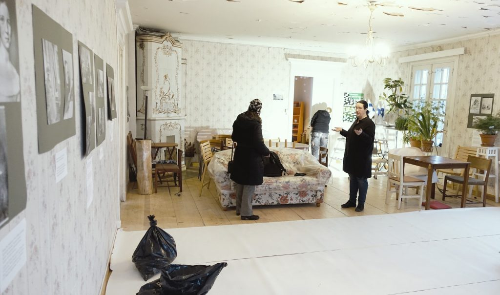 Annalan huvilan projektikoordinaattori Jaana Merenmies keskustelee huvilan salissa vierailijan kanssa. Salin huonekalut ja -kasvit on siirretty syrjään kattoremontin tieltä.