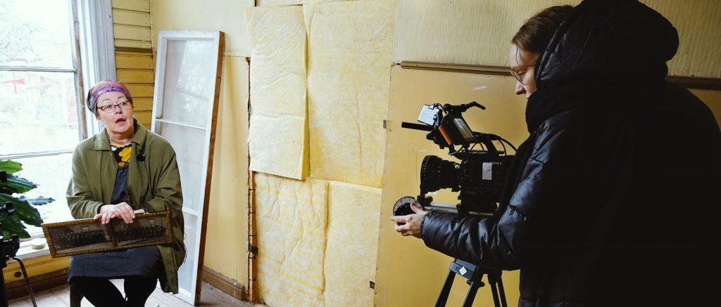 Metropolian opiskelija kuvaa videokameralla haastateltavaa Perinnetalkoot-dokumenttia varten.