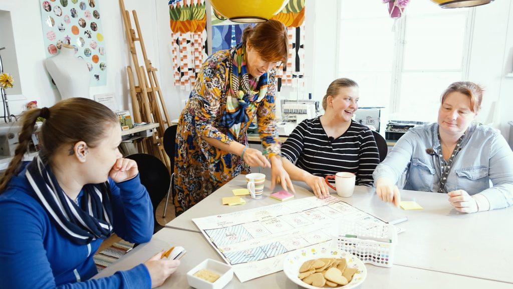 Perinnetalkoot-hankkeen työntekijät tutkivat vanhan maamieskoulun pohjapiirroksia pöydän ääressä.