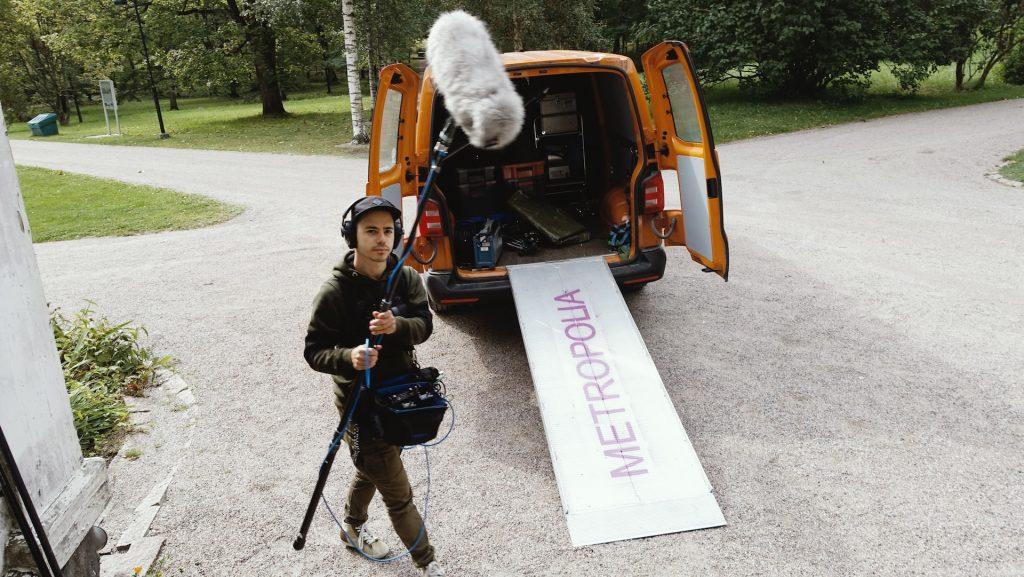 Metropolian opiskelija pitkään puomiin kiinnitetyn mikrofonin kanssa ulkokuvauksissa Annalan huvilan vehreällä puistoalueella. Metropolian oranssin pakettiauton takaluukku on auki ja tavaratilassa näkyy kuvauksissa tarvittavaa välineistöä.