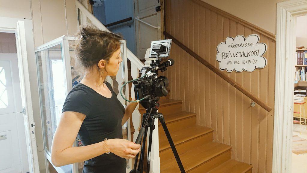 Metropolian opiskelija kuvaa jalustalla olevalla videokameralla Perinnetalkoot-toiminnasta kertovaa kylttiä. Kyltti on Lapinjärven vanhan maamieskoulun yläkertaan vievän portaikon seinällä. Kuvan oikeassa laidassa näkyvästä oviaukosta on näkymä yhteen rakennuksessa nykyisin toimivan Lapinjärven kirjaston huoneista.