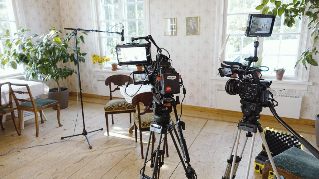 Annalan huvilan sali remontin myöhemmässä vaiheessa. Tilaan on tuotu huonekaluja ja kaksi kookasta viherkasvia, seinillä on vaalea, kukkakuvioinen tapetti ja valokuvia. Kuvan etualalla on kaksi videokameraa. Taka-alalle on asemoitu kaksi tuolia ja mikrofoni haastattelua varten.