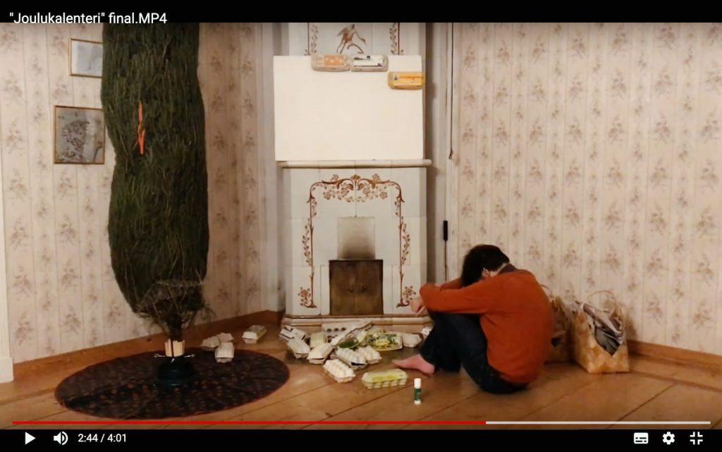 Näyttökuva Joulukalenteri-elokuvasta. Punapuseroinen poika istuu puulattialla kaakeliuunin edessä pää polviin painettuna. Pojan edessä on kasa tyhjiä munakennoja ja vieressä verkolla peitetty joulukuusi.