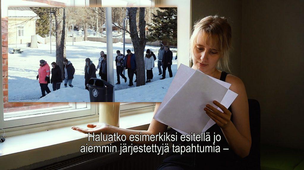Kuvakaappaus ohjevideosta: henkilö tutkii esittelyvideon käsikirjoitusta ikkunan äärellä.